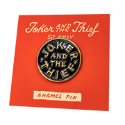 Transparent background photograph of the insignia pin reading Joker and the Thief on its bright red backing card