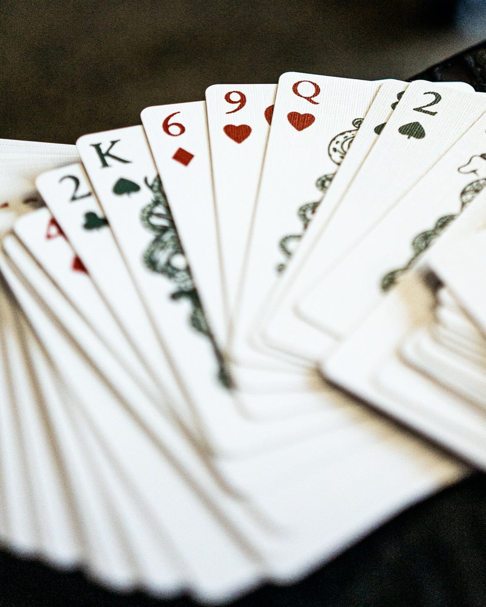close up photo of numbers and pips of a deck of playing cards