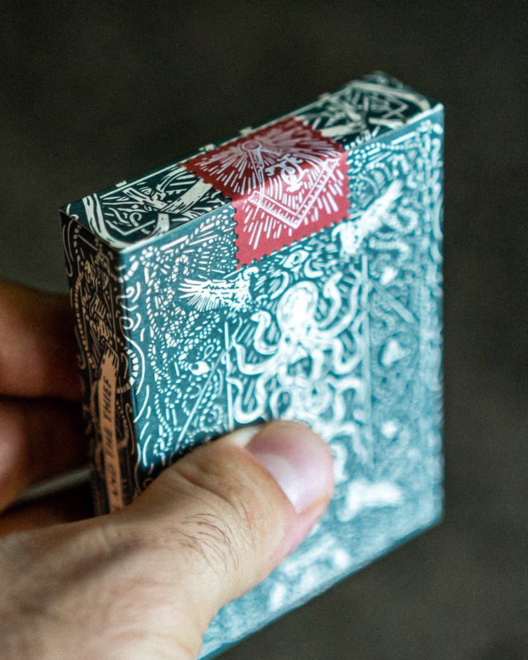 Close up image of hand holding a sealed deck of green seafarers playing cards, displaying the back of the packaging and a red and white sticker seal in a classic tax-stamp style