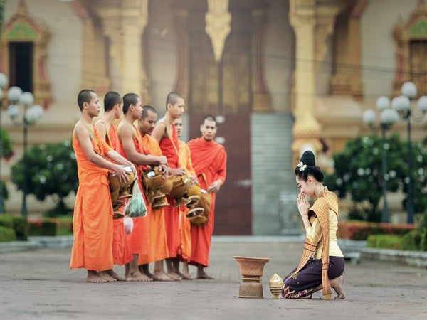 charity- woman bows down to the buddhist monks