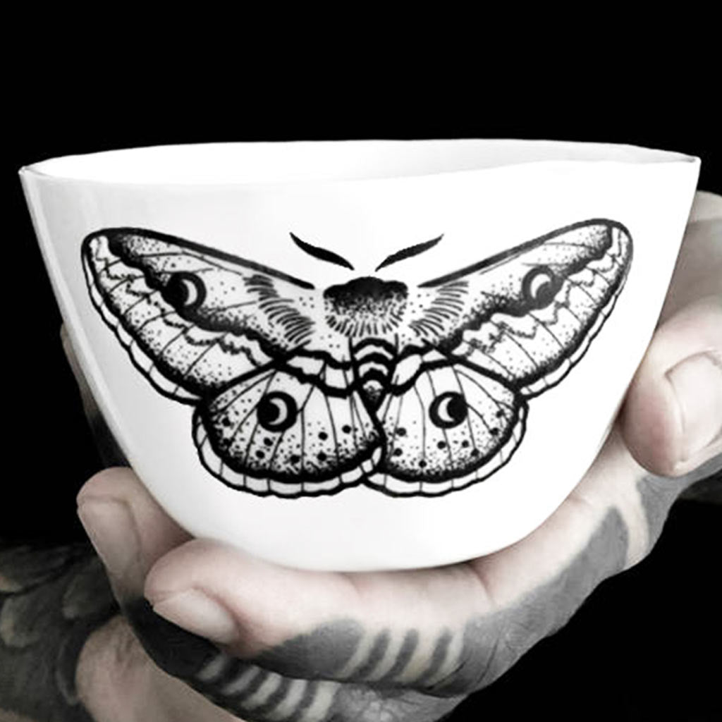 A translucent porcelain cup decorated with a black butterfly