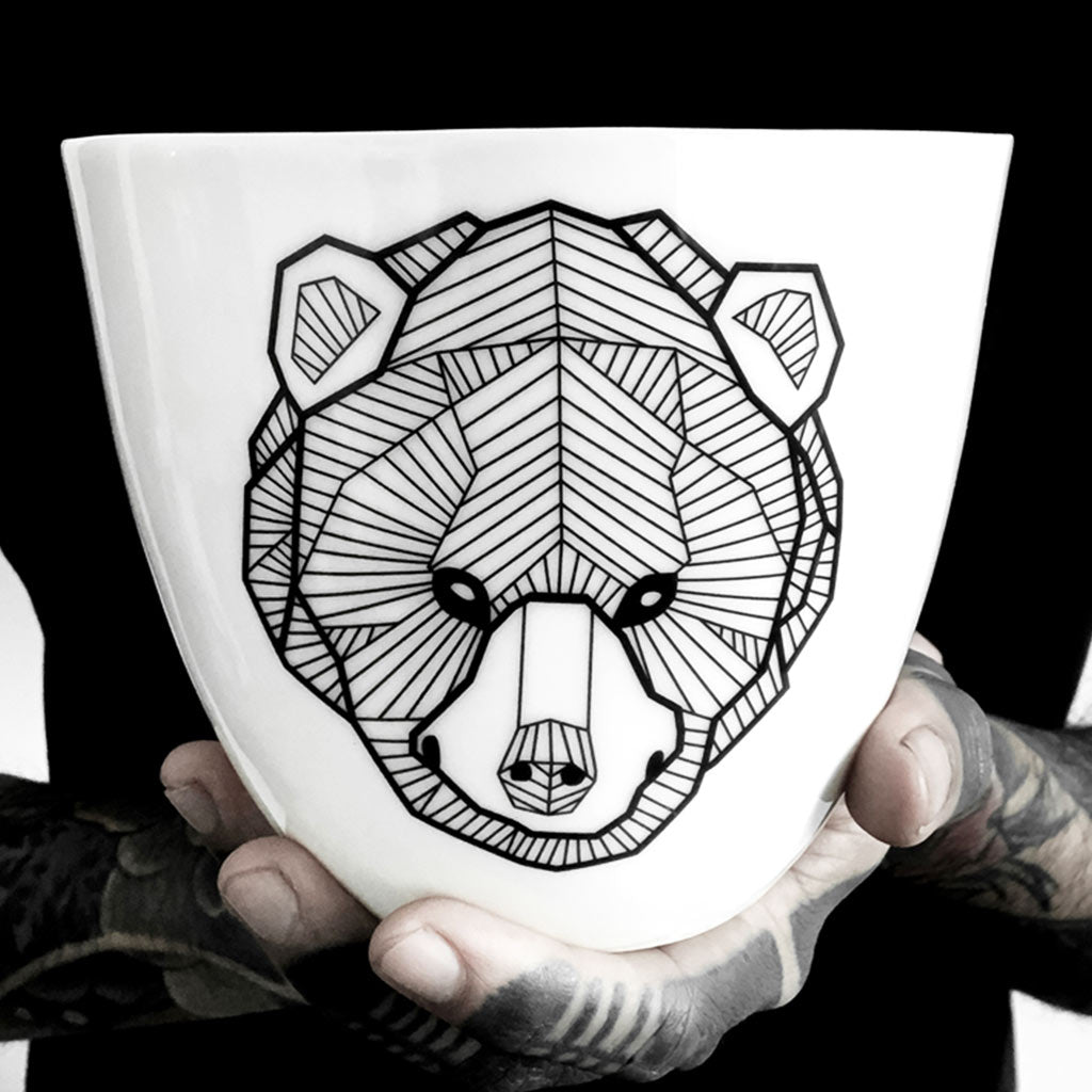 A porcelain mug decorated with a black bear