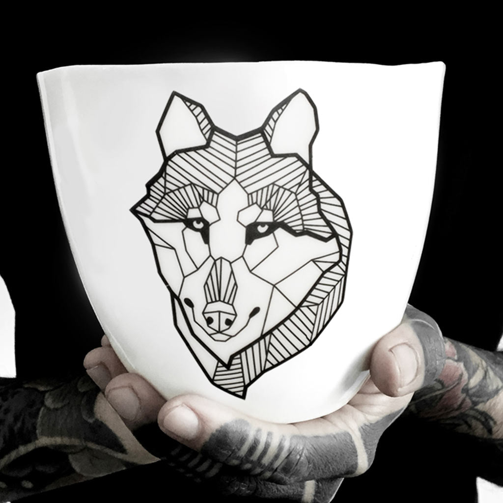 A porcelain mug decorated with a black lined wolf