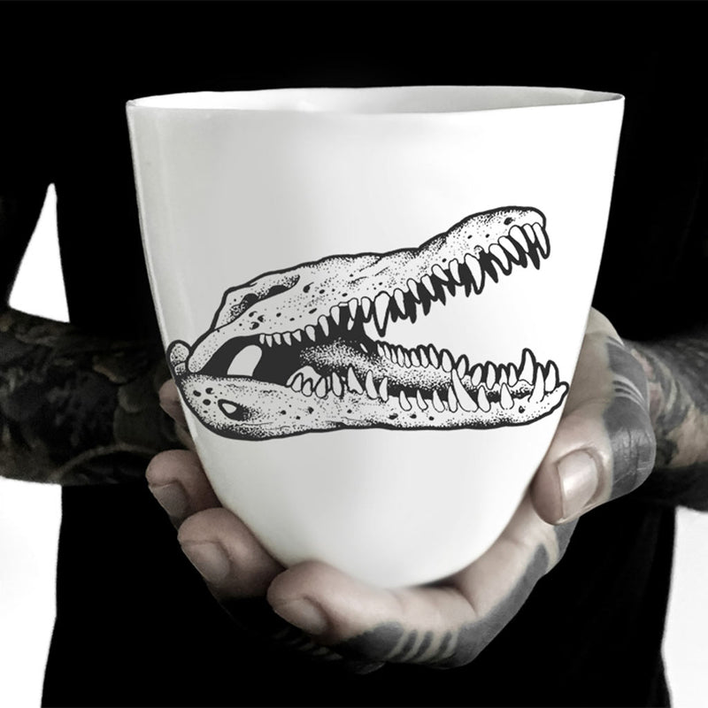 A translucent porcelain mug decorated with a black crocodile