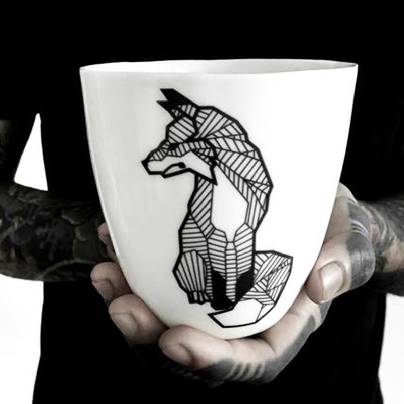 A porcelain mug decorated with a black fox