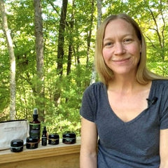 Rachel Powell Founder of BEAUTY IN THE Raw on porch with products