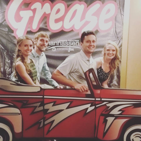 Four adults in a car without a Wipermoji sticker in front of a large sign for the play Grease