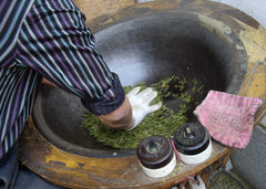 Lung Ching Dragonwell tea being pressed dry by a tea master
