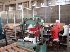 Tea beengs being manufactured using a hydraulic press in a Yunnan Province tea factory