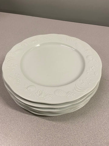White dinner plates with white fruits around the trim