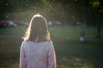 Woman standing facing away from the photo in the sunlight, with what appears to be bugs or dust glimmering in the sunlight.