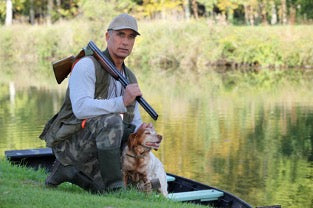 Man by the water with his dog, presumably about to set off on the water to hunt.