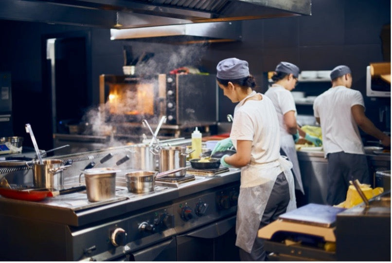 3 members of a restaurant staff preparing a meal in a kitchen.