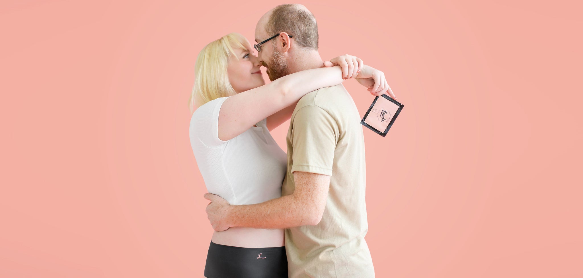 Curvy woman hugging man with beard. Woman is wearing latex underwear and holding packet of Lorals