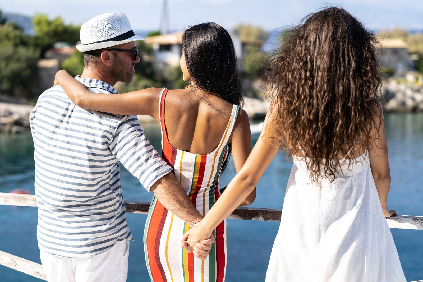 Image of a man with arm around a woman while holding hands with another woman