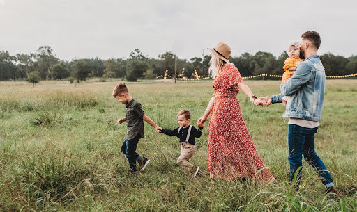 Couple with 3 children walking in a field