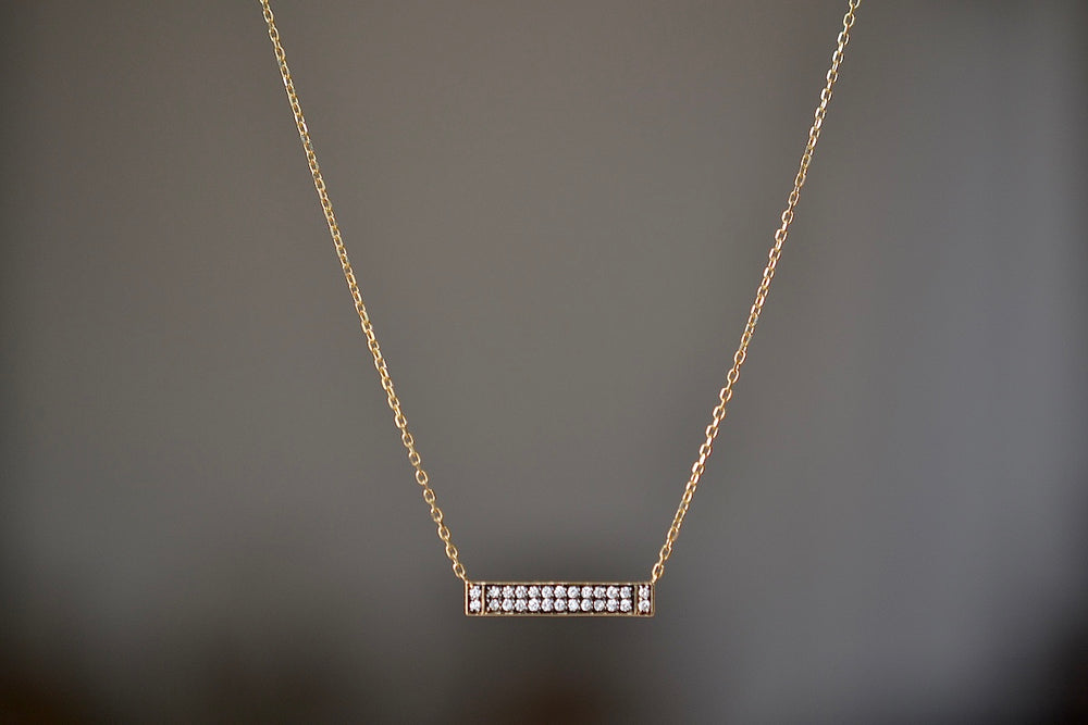 Sorellina Otto Diamond Bar Necklace Pendant is a bezel set horizontal bar of rhodium plating with 26 twenty-six  white pave pavé diamonds in 18k yellow gold.