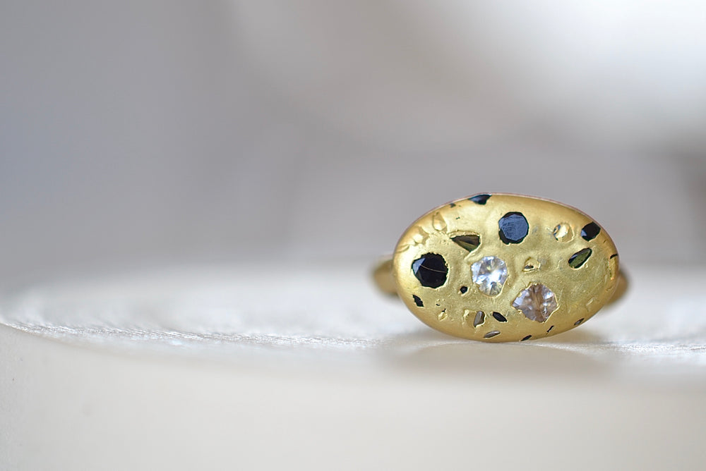 Polly Wales Elysian Ring with knife edge band in 18k recycled yellow gold with black and white sapphires and cast not set