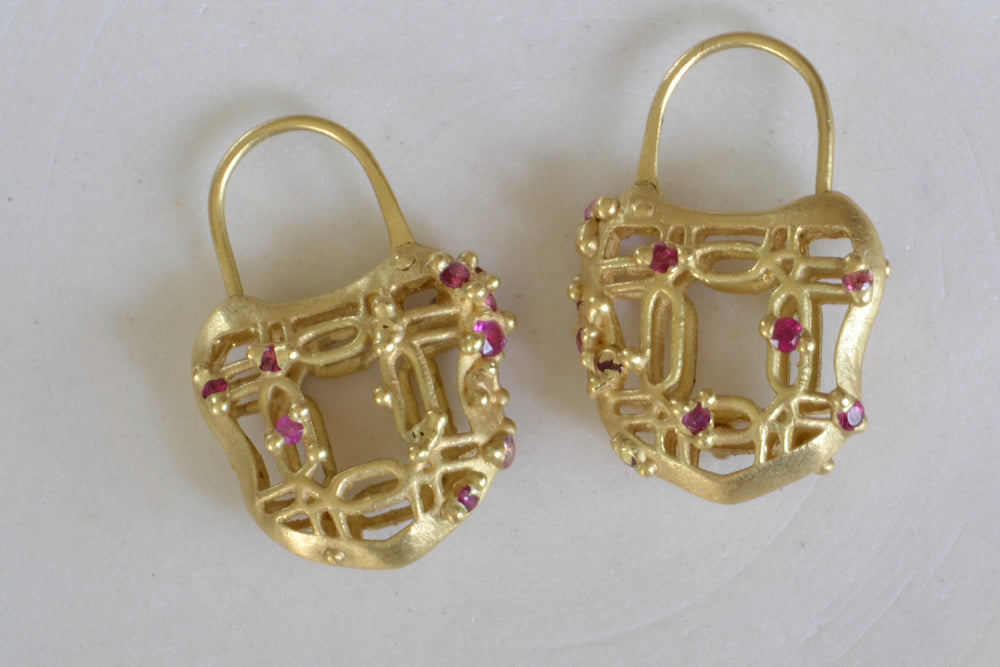 Polly Wales Coeur de Dentelle Padlock Earrings 18k yellow gold filagree padlock earrings with rich pink sapphires and a matte finish. Hinged ear wire closure