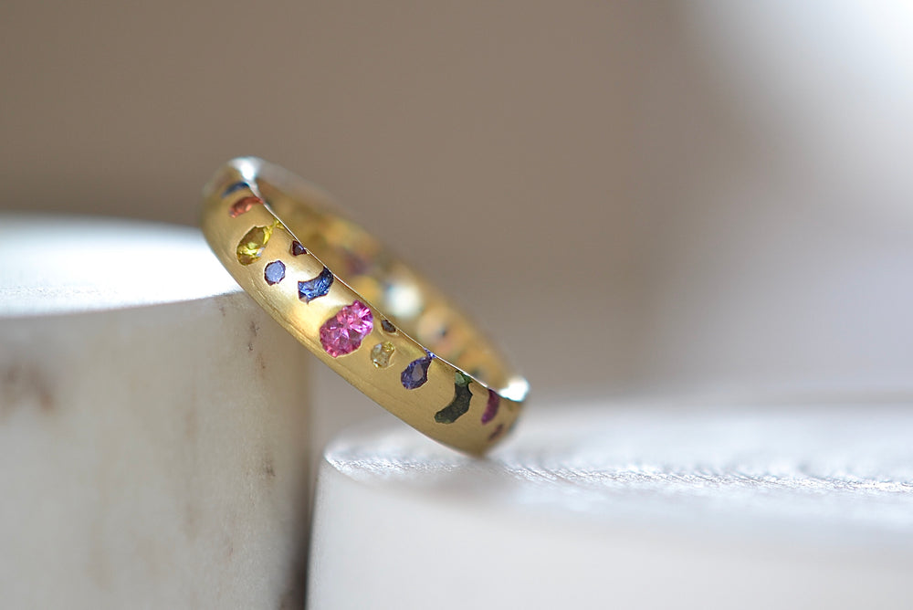 Polly Wales Classic Rainbow Confetti Band Ring in 18k recycled yellow gold with green, yellow, orange, blue, purple and pink sapphires and cast not set