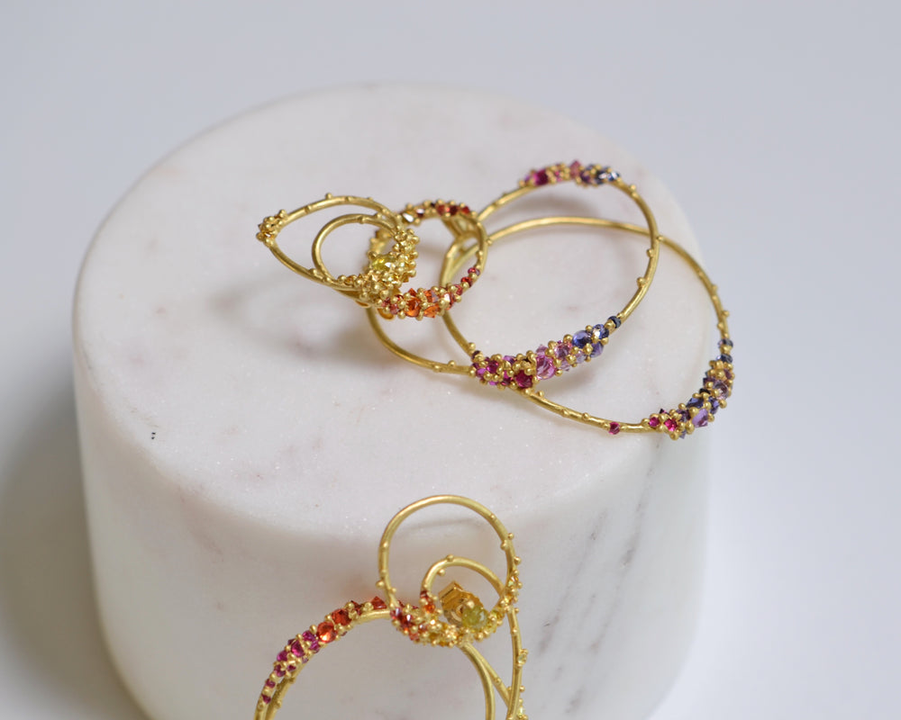 Polly Wales Estelle Earrings in Supernova pink, red, purple, yellow and orange sapphires 18k yellow recycled gold statement earrings