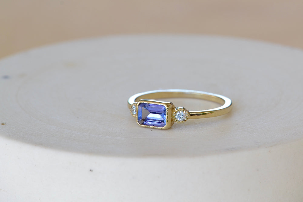 Jennie Kwon Lexie Tanzanite Ring Emerald Cut rectangular bezel set purple flanked by two round white diamonds with milgrain engraved detail on square 14k yellow gold band