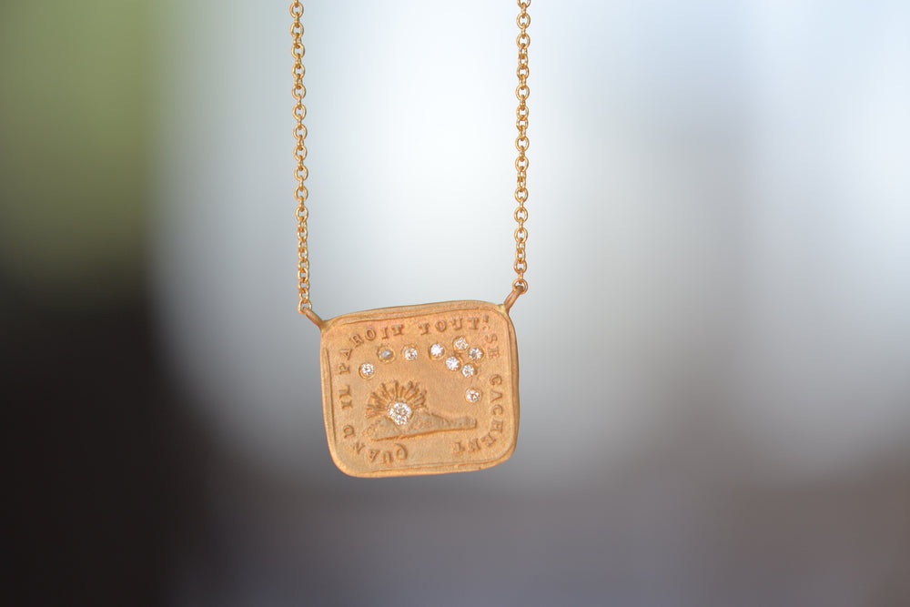 Makiko Wakita Motto Conceals All Necklace A pendant with satin finish on a 14k gold chain image of the sun and stars with 10 ten diamonds : Quand II Paroit Tout Se Cachent, meaning, 'When it Appears, It Conceals All