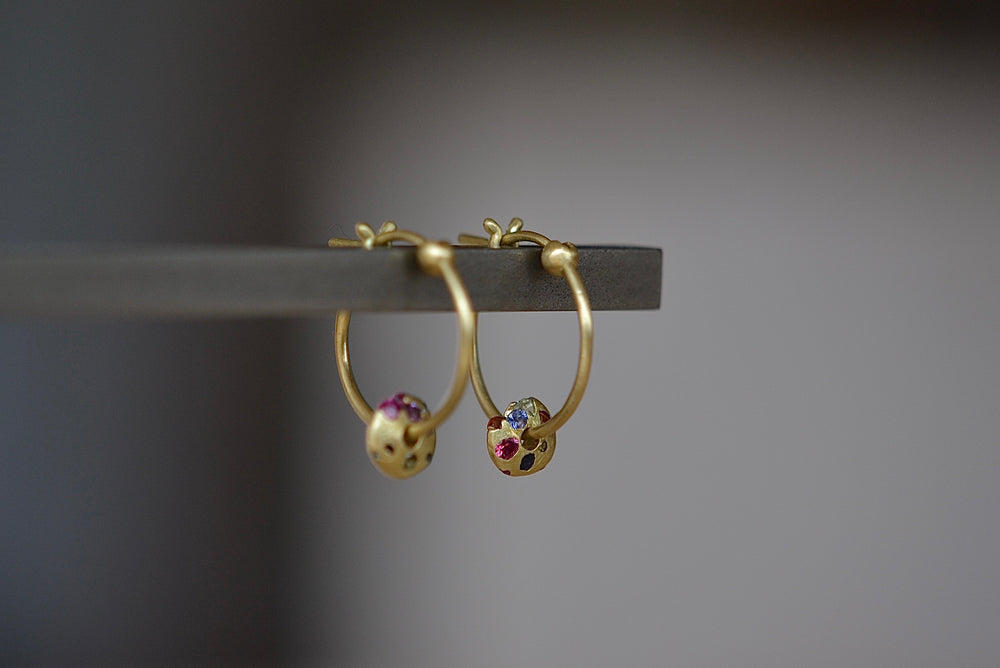 Polly Wales Rainbow Sapphire Spinner Hinge Hoop Earrings in 18k yellow recycled gold with disc speckled with rainbow sapphires confetti style in pink, purple, blue, black orange and yellow. Hinge lock. Cast not set. One of a kind.