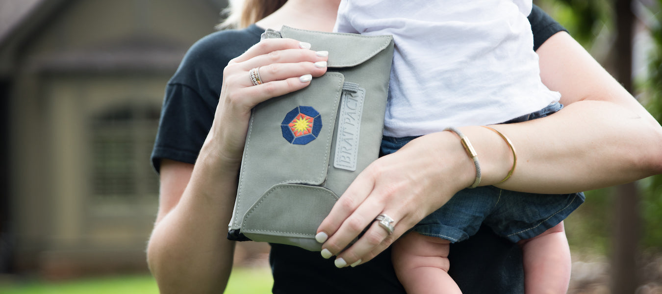 Woman holding bratpack diaper bag and baby