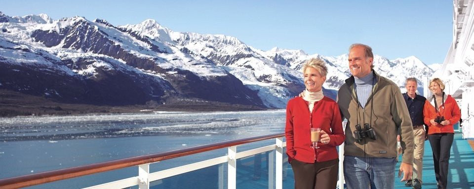 Adults on deck sightseeing on an Alaskan cruise