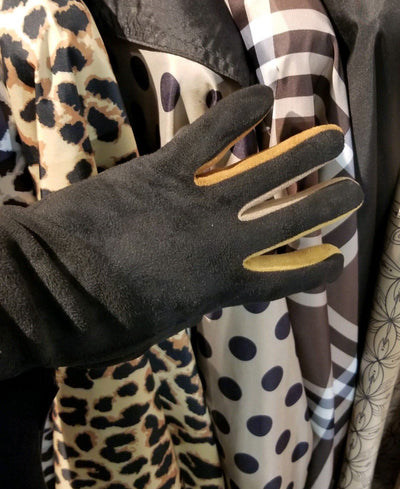 A gloved hand wearing black texting gloves with neutral colored gussets between each finger. The hand is in front of an array of neutral color RainCapers.