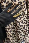 A gloved hand wearing black texting gloves with neutral colored gussets between each finger. The hand is in front of a leopard print RainCaper.