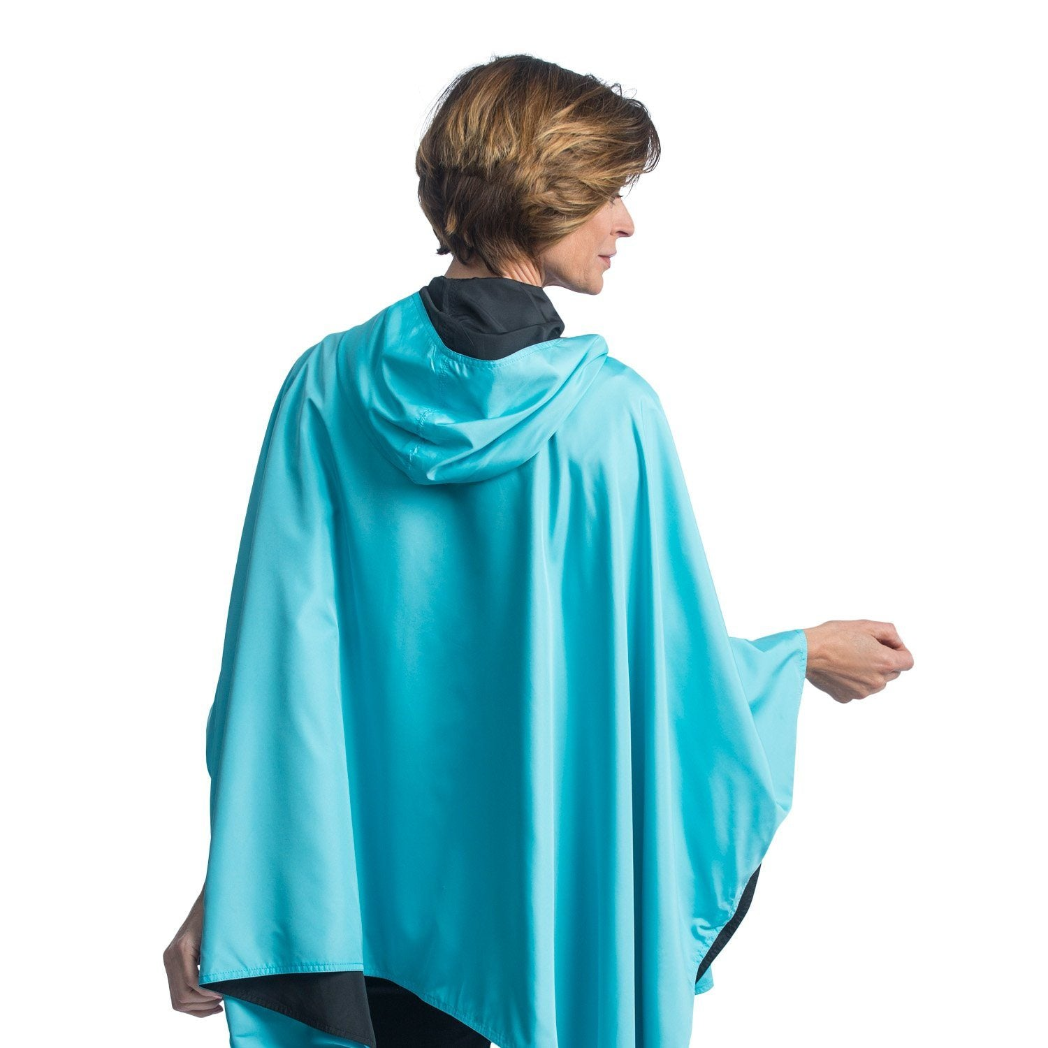 Women wearing a Black & Sky Blue RainCaper travel cape with the Black side out, revealing the Sky Blue print at the lapels and cuffs.
