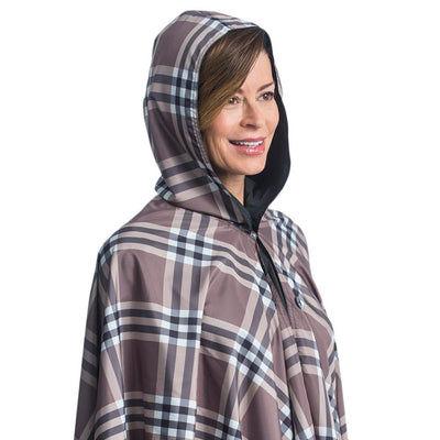 Women wearing a hooded Black & Coco Plaid RainCaper travel cape with the Coco Plaid print side out
