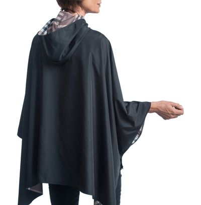 Women wearing a Black & Coco Plaid RainCaper hooded travel cape with the black side out