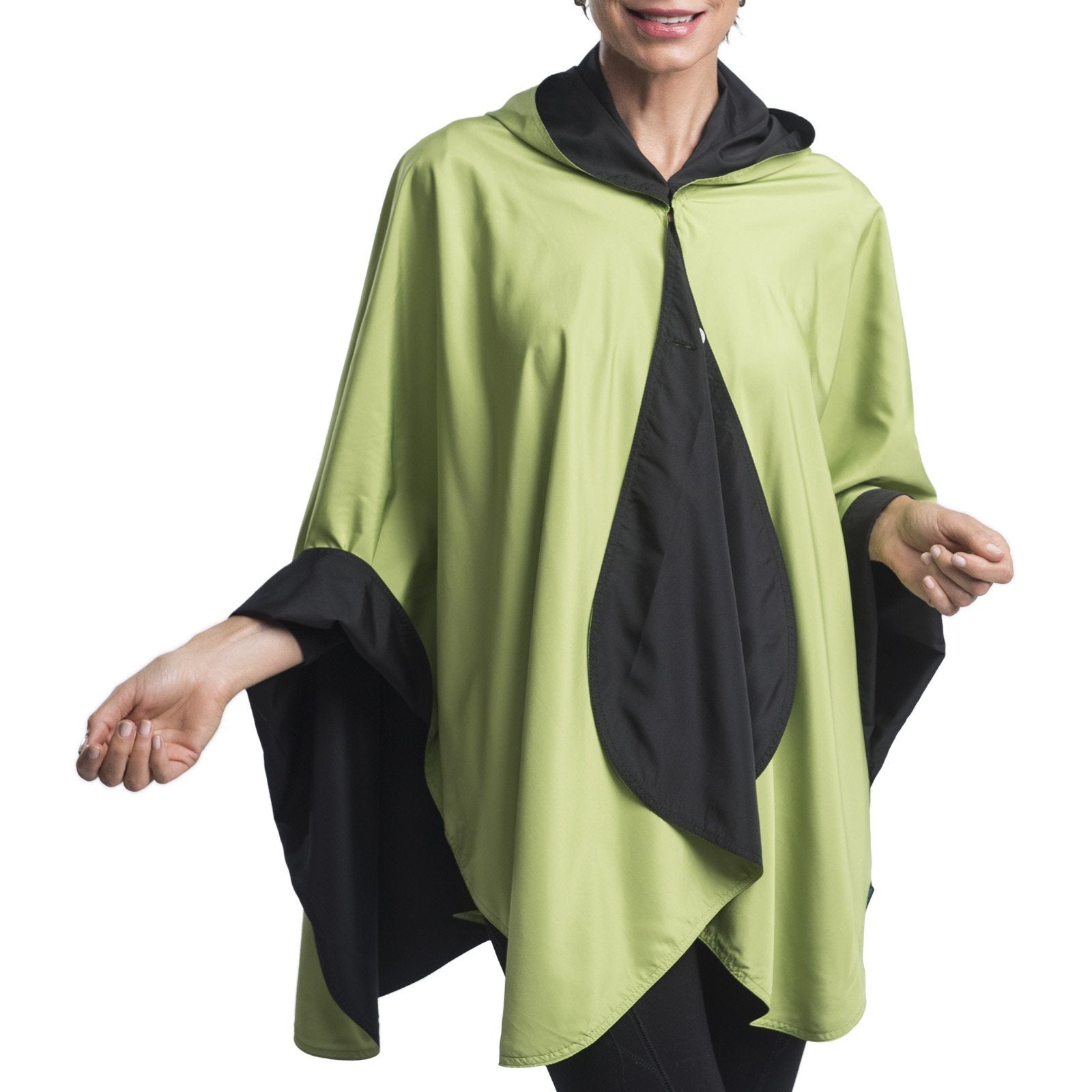 Women wearing a Black & Greenery RainCaper travel cape with the Black side out, revealing the Greenery color at the lapels and cuffs.