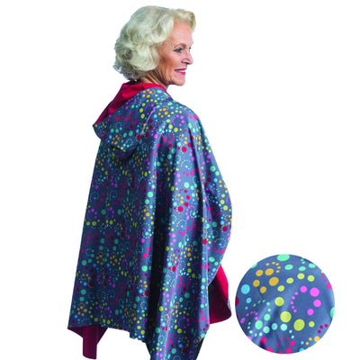 Woman wearing a RainCaper Swirl Dots cape which reverses to Berry. She is standing with a blow-up of the Swirl Dots print detail.