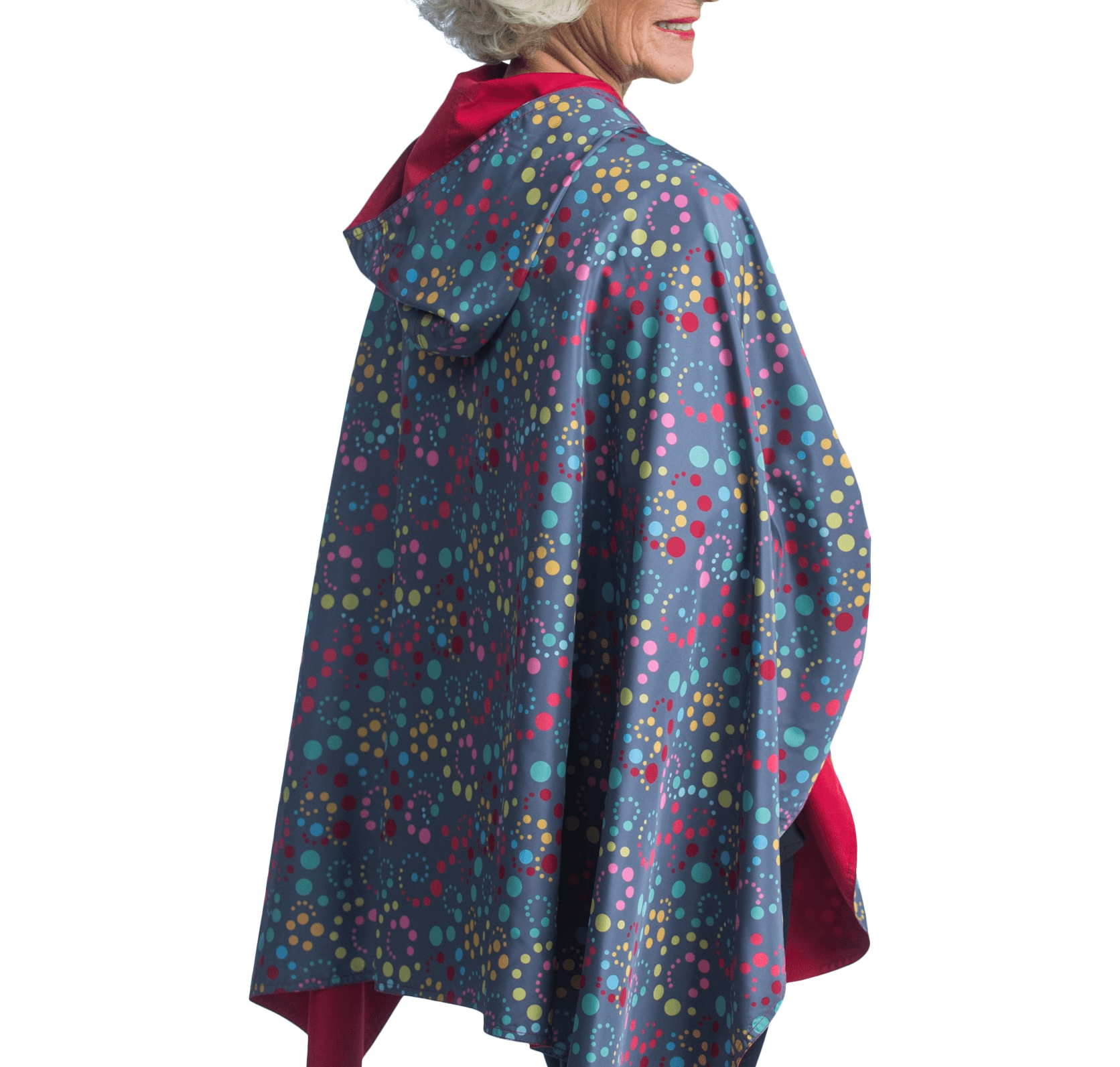 Women wearing a Berry and Swirl Dots RainCaper travel cape with the Swirl Dots side out, revealing the Berry side at the lapels, neckline and cuffs.