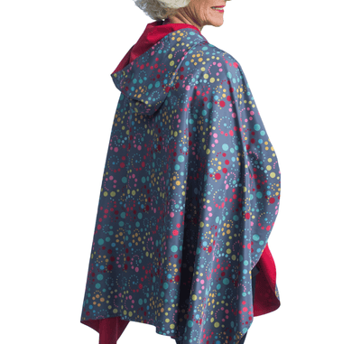 Women wearing a Berry & Swirl Dots RainCaper travel cape.
