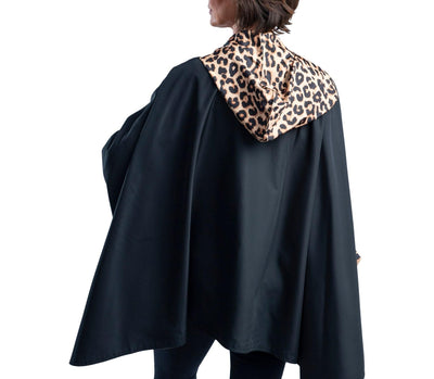 Women wearing a Black & Leopard Animal Print RainCaper hooded travel cape with the black side out