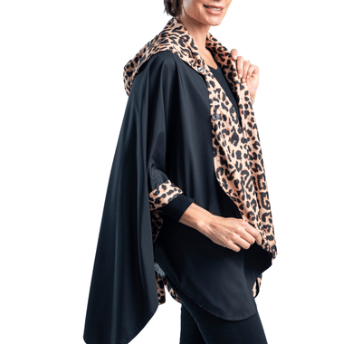 Women wearing a Black & Leopard Animal Print RainCaper travel cape with the Black side out, revealing the Leopard Animal print at the lapels and neck