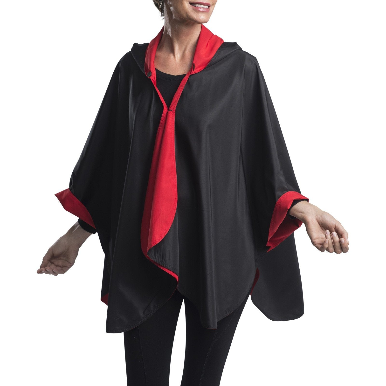 Women wearing a Black & Red RainCaper travel cape with the Black side out, revealing the Red color at the lapels and cuffs