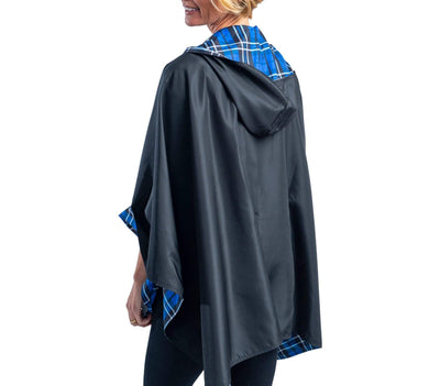 Women wearing a Black & Royal Tartan RainCaper hooded travel cape with the black side out
