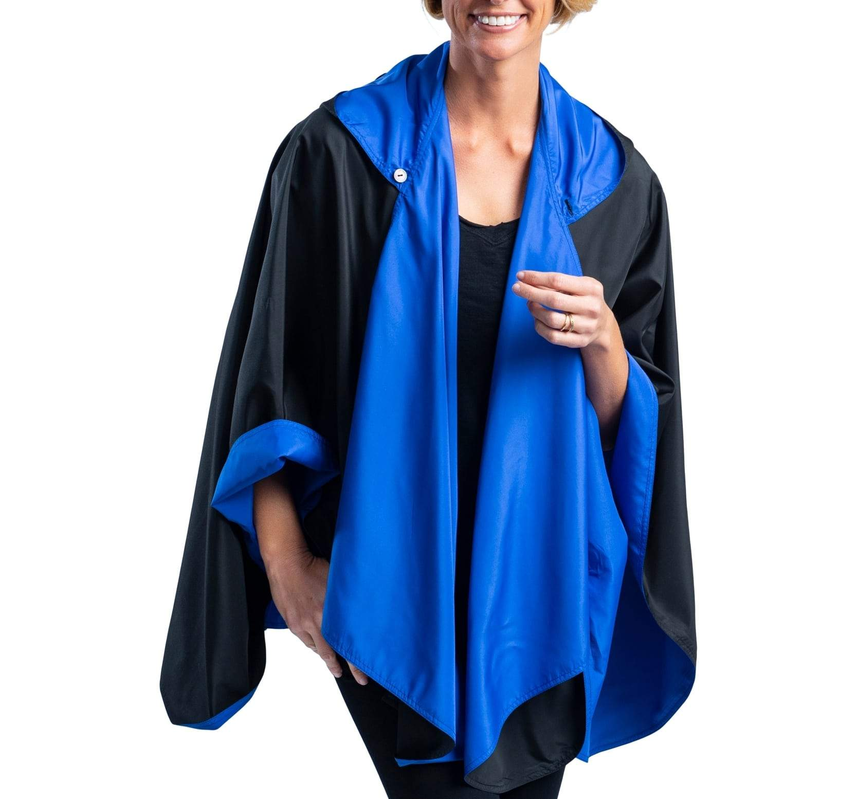 Woman wearing a Black/Royal Blue RainCaper travel cape with the Black side out, revealing the Royal Blue print at the lapels and cuffs