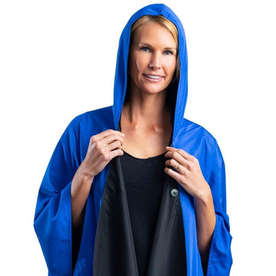 Women wearing a hooded Black/Royal Blue RainCaper travel cape with the Royal Blue print side out
