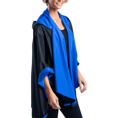 Women wearing a Black/Royal BlueRainCaper travel cape with the Black side out, revealing the Royal Blue print on the hood and cuffs