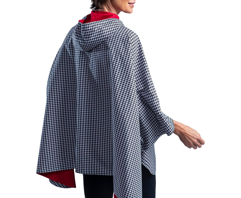 Women wearing a Crimson/Black & White Houndstooth RainCaper travel cape with the White Houndstooth side out, revealing the Crimson side at the lapels, neckline and cuffs
