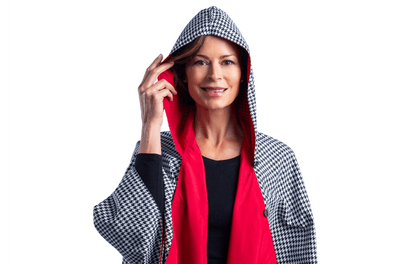 Women wearing a hooded Crimson/Black & White Houndstooth RainCaper travel cape with the Black & White Houndstooth print side out