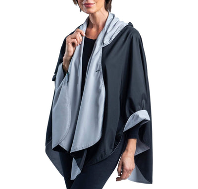 Women wearing a Black & Pewter Grey RainCaper travel cape with the Black side out, revealing the Pewter Grey at the lapels and cuffs
