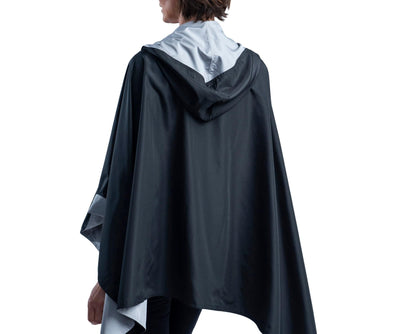 Women wearing a Black & Pewter Grey RainCaper hooded travel cape with the black side out